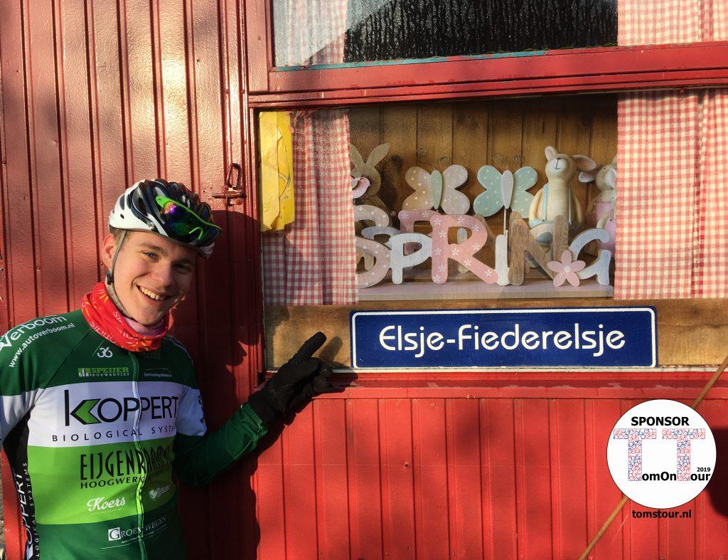 Tom wijst vrolijk naar het bord van Elsje-Fiederelsje, zijn nieuwste sponsor die weet wat gedrevenheid is.