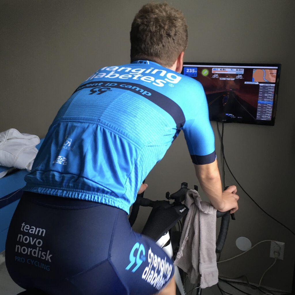 Ik op mijn Wahoo Kickr tijdens een Zwift race, die ik, tijdens het trappen, kan volgen op het beeldscherm voor mij.